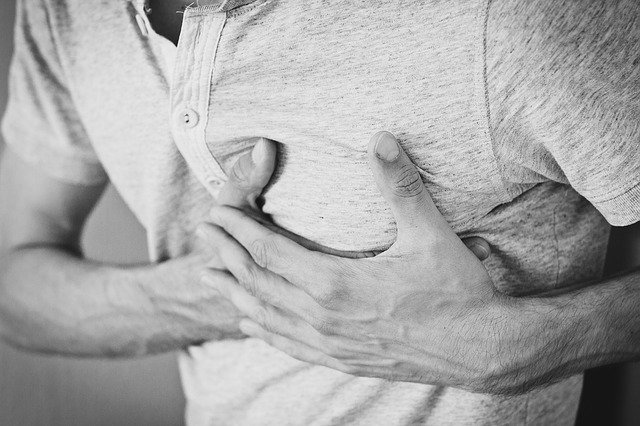 Man with lupus with hands on his chest during a heart attack
