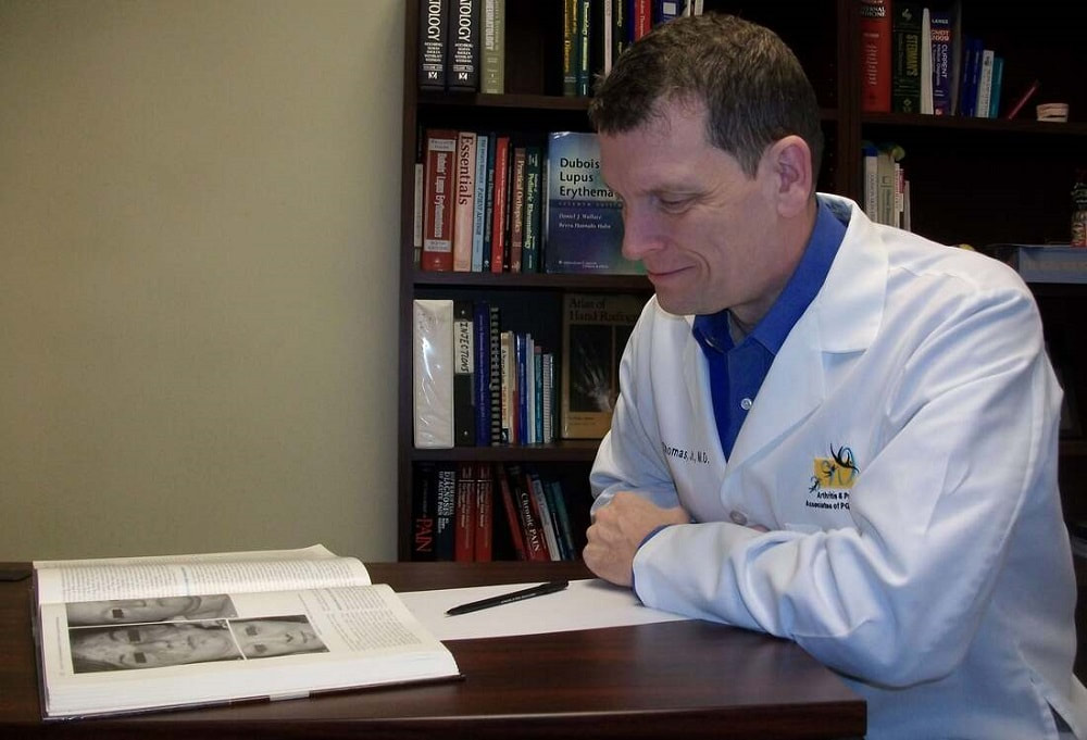 Dr. Donald Thomas author of The Lupus Encyclopedia in white lab coat reading a book on lupus in a library