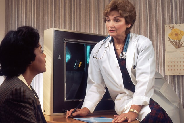 A middle aged white female doctor in a white lab coat talking to a black female lupus patient about a lupus diagnosis